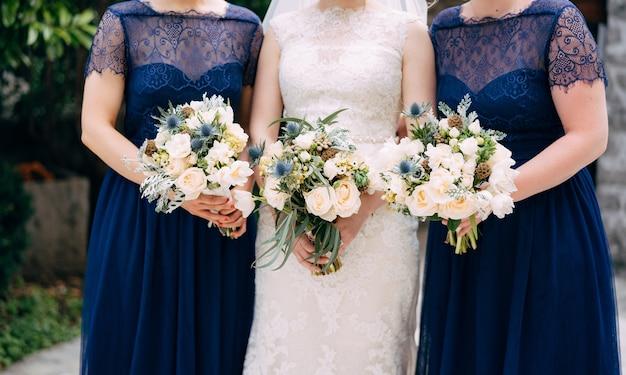 Panna młoda i druhny w identycznych niebieskich sukniach stoją obok siebie i trzymają bukiety w