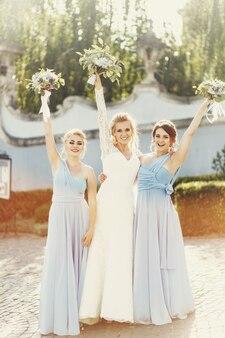 Panna młoda i druhny w niebieskich sukienkach podnoszą ręce z bukiecikami na zewnątrz