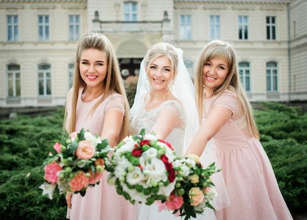 Panna młoda i druhny w różowych sukienkach wyciągają dłonie z bukiety ślubne