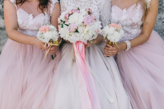 Panna młoda i dziewczyny w różowej sukience z bukietami na weselu.