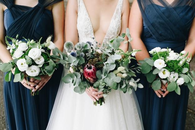 Panna młoda i jej druhny trzymające przed sobą bukiety kwiatów
