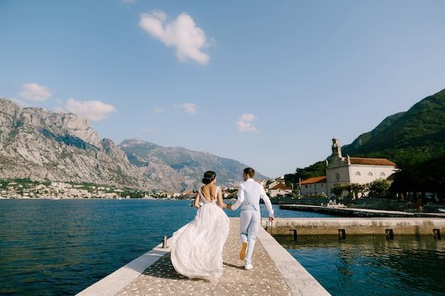 Panna młoda i pan młody biegają wzdłuż molo w zatoce kotorskiej, trzymając się za ręce widok z tyłu