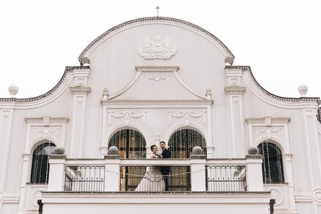 Panna młoda i pan młody na balkonie pięknego hotelu