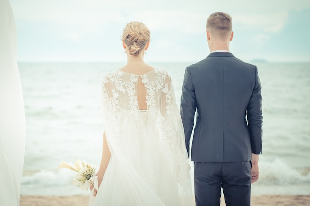 Panna młoda i pan młody na plaży z romantyczną chwilą