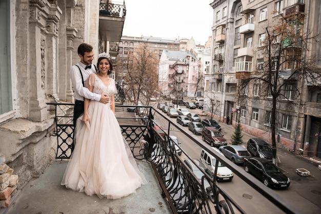 Panna młoda i pan młody obejmują się na balkonie. para przytulająca się na balkonie i ciesz się życiem
