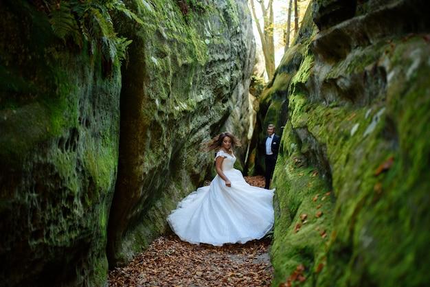 Panna młoda i pan młody para spacerująca wśród wąskiego pięknego wąwozu. wąwóz porośnięty był zielonym mchem. nowożeńcy wirują i biegają