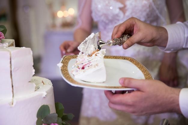 Panna młoda i pan młody pokroili tort weselny. ciasto zdobią beżowe i zielone róże.