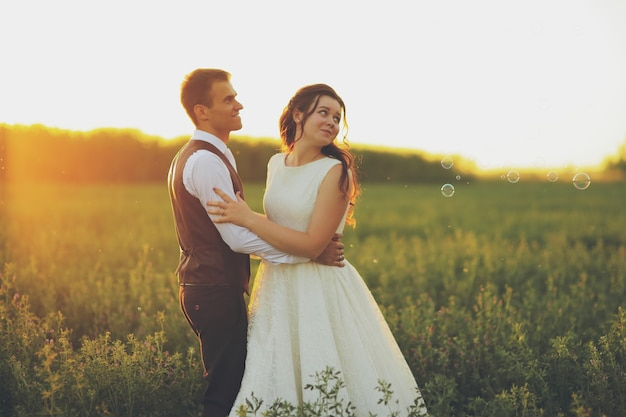 Panna młoda i pan młody przytulają się w parku w świetle zachodzącego słońca