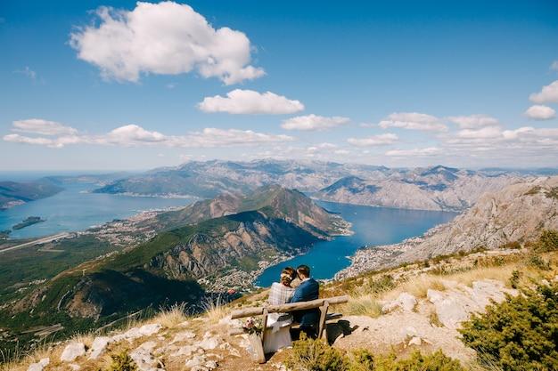 Panna młoda i pan młody siedzą na ławce i patrzą na zatokę kotorską wspaniały widok z