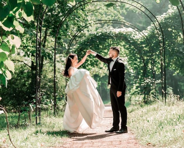 Panna młoda i pan młody tańczą pod łukiem ślubnym