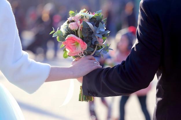 Panna młoda i pan młody trzyma bukiet ślubny