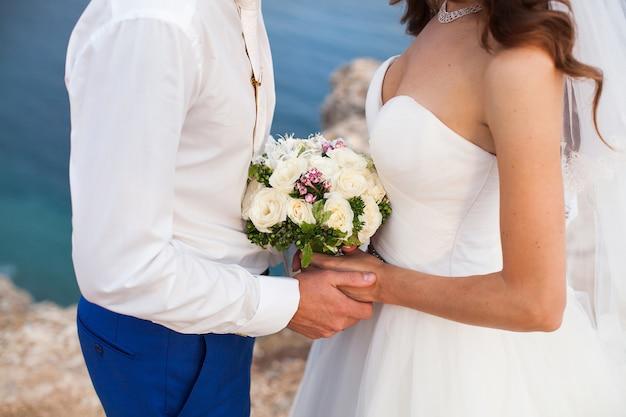 Panna młoda i pan młody trzyma ślubny bukiet kwiatów