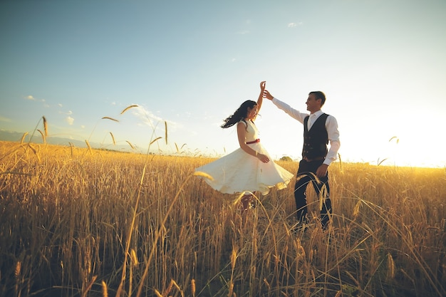 Panna młoda i pan młody trzymają się za ręce, tańcząc w parku.