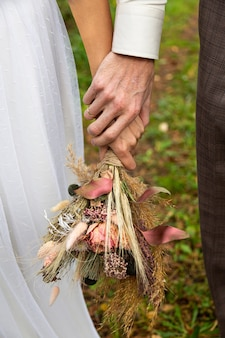Panna młoda i pan młody trzymają się za ręce. w rękach bukiet suszonych kwiatów w stylu boho