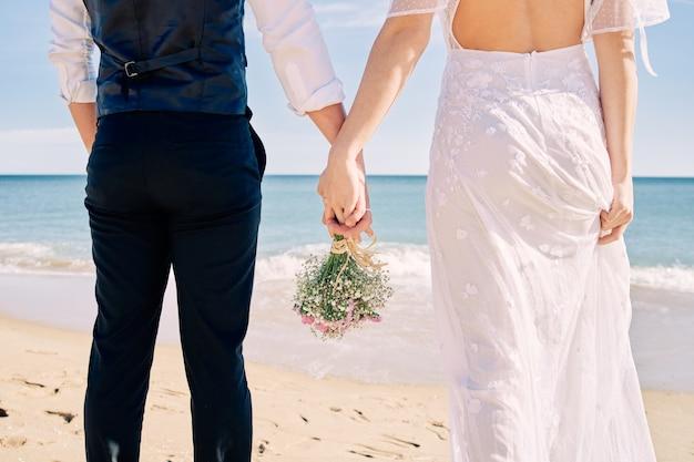 Panna młoda i pan młody, trzymając się za ręce na plaży w sukniach ślubnych