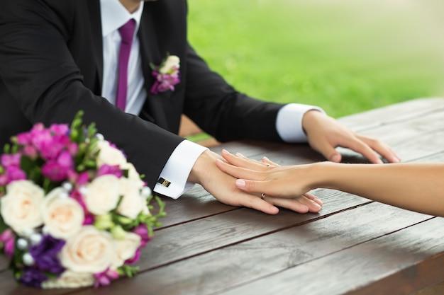 Panna młoda i pan młody trzymający się za ręce na stole
