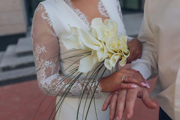 Panna młoda i pan młody trzymający się za ręce obrączki ślubne i szczegóły bukietu narzeczonych