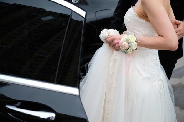 Panna młoda i pan młody w pięknej białej sukni wsiadają do czarnego samochodu. nowożeńcy obok samochodu.