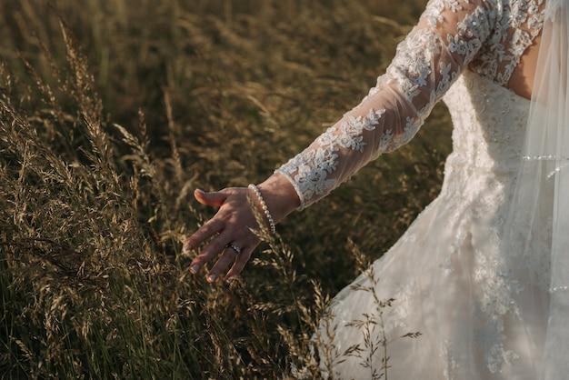 Panna młoda idzie w polu pszenicy ubrana w piękną suknię ślubną i bransoletkę z pereł