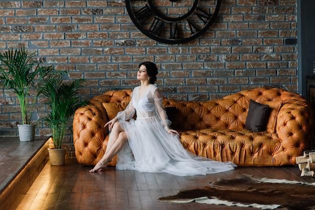 Panna młoda jest brunetką o europejskim wyglądzie. pojedynczy portret. makijaż ślubny i fryzura. poranek panny młodej. buduar w hotelu.
