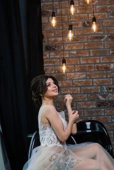 Panna młoda jest brunetką o wyglądzie europejczyka. pojedynczy portret. makijaż ślubny i fryzura. poranek panny młodej. buduar w hotelu.