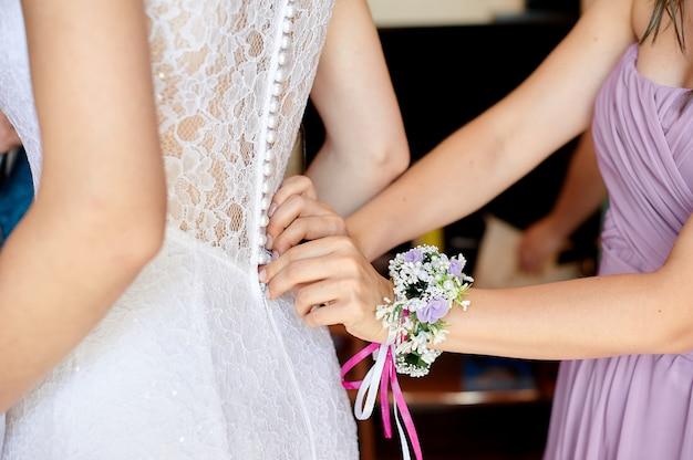Panna młoda jest ubranym ślubną białą suknię. pomagając pannie młodej ją położyć. druhny ubierają sznurówki z tyłu