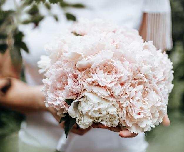 Panna młoda kobieta trzyma bukiet ślubny kwiatów