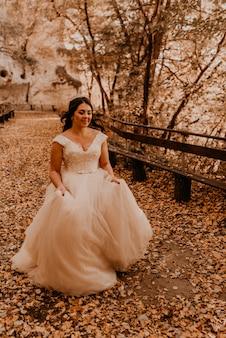 Panna młoda kobieta w białej sukni ślubnej z makijażem fryzury i koroną na głowie idzie przez jesienny las na opadłych liściach pomarańczy