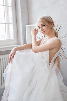 Panna młoda kobieta w lekkiej letniej sukni ślubnej siedzi przy oknie i czeka na ceremonię ślubną