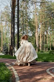 Panna młoda kobieta w luksusowej bufiastej sukni ślubnej biegnie ścieżką do ślubu