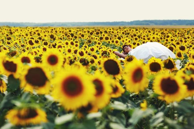 Panna młoda leży na słoneczniki w słoneczny dzień