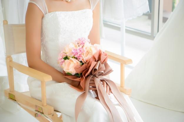 Panna młoda miała na sobie suknię ślubną, siedząc na krześle i trzymając bukiet kwiatów. ma zamiar rzucić bukiet ślubny jednej przyjaciółce.