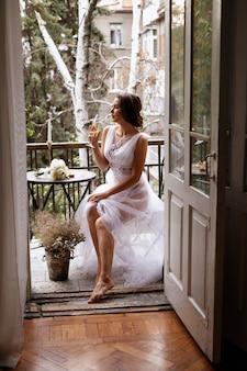 Panna młoda na balkonie z lampką szampana