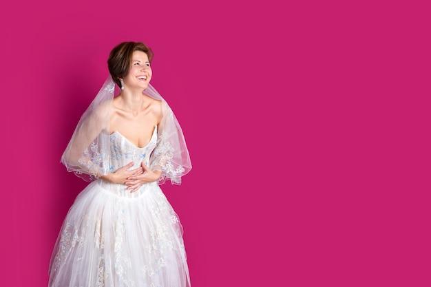Panna młoda na różowym tle kobieta ubrana w suknię ślubną z koronkowym copyspace na tekst