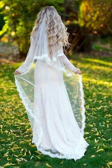 Panna młoda o blond włosach w sukni ślubnej poprawiła zasłonę plecami