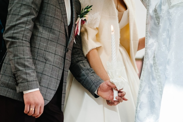 Panna młoda, pan młody trzyma w rękach świecę ślubną. zapal świecę. duchowa para trzymająca świece podczas ceremonii ślubnej w kościele chrześcijańskim. ścieśniać.
