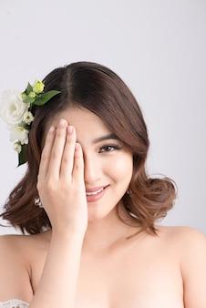 Panna młoda piękna azjatykcia kobieta na szarym tle. portrety z bliska z profesjonalnym makijażem
