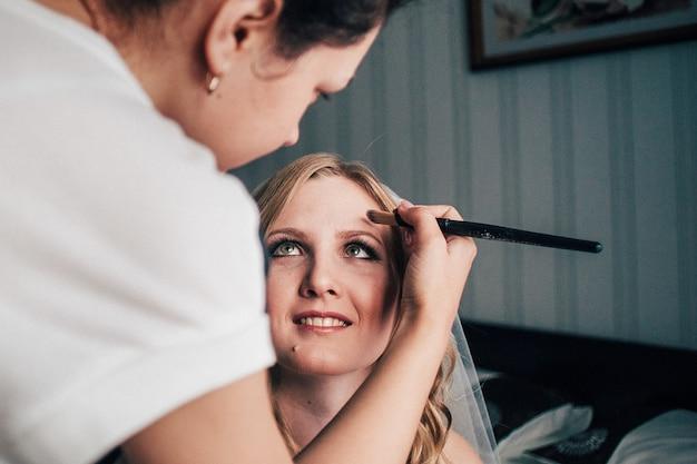 Panna młoda piękna w bridal welon siedzi na łóżku. wizażystka robi makijaż. pędzel maluje twarz. seksowna modelka w pomieszczeniu. piękna kobieta z kręconymi włosami. portret kobiety panna młoda rano słodkie damy