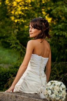 Panna młoda pozowanie w ogrodzie z białą suknią ślubną