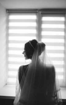 Panna młoda pozuje przeciw okno pokazuje ona z powrotem