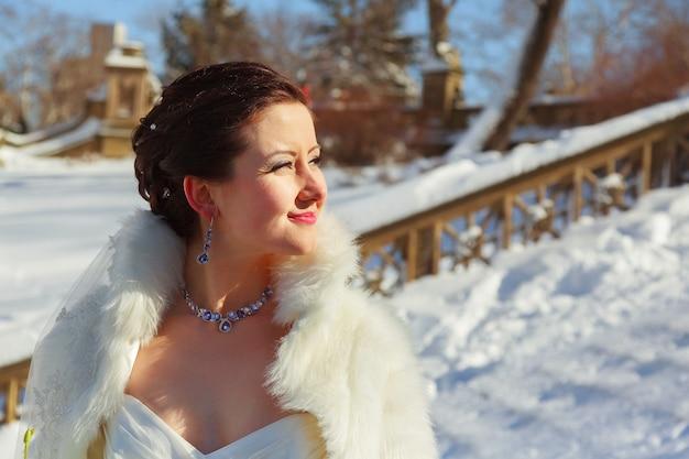 Panna młoda pozuje w zimowym lesie w futrze. ślubna sesja zdjęciowa w zaśnieżonym parku.