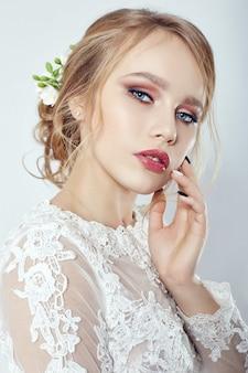 Panna młoda przed ceremonią ślubną, idealna figura panny młodej, piękny makijaż i włosy. panna młoda w luksusowej białej sukni ślubnej i pięknej fryzurze