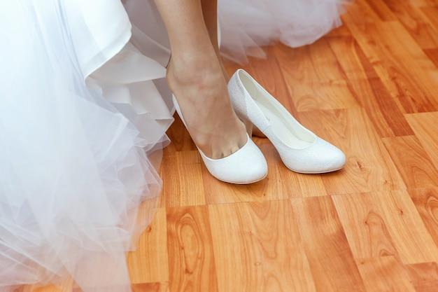 Panna młoda przygotowuje się do ceremonii noszenia pięknych butów na piechotę w dniu ślubu. deklaracja miłości, wiosna. poranne wesele chwile koncepcja szczegółów.