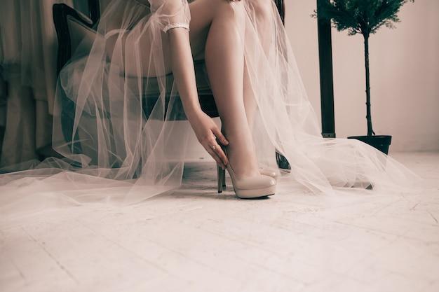 Panna młoda przymierza eleganckie buty ślubne.