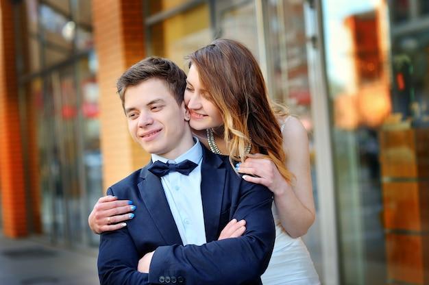 Panna młoda przytula ramiona pana młodego na ulicy
