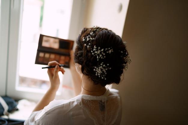 Panna młoda robi makijaż stojąc przy oknie w pokoju hotelowym przed ceremonią ślubną