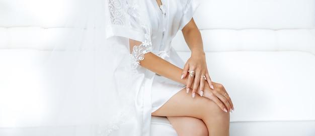 Panna młoda siedzi na kanapie w białych szatach z rękami na kolanach. piękny manicure. eleganckie paznokcie. złote pierścienie. biżuteria ślubna.