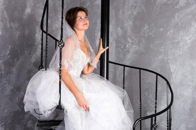 Panna młoda siedzi na spiralnych schodach w mieszkaniu na poddaszu kobieta ubrana w suknię ślubną z koronkową kopią sp...
