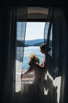 Panna młoda siedzi przy otwartym oknie z widokiem na morze i trzepoczącymi zasłonami i trzyma bukiet ślubny