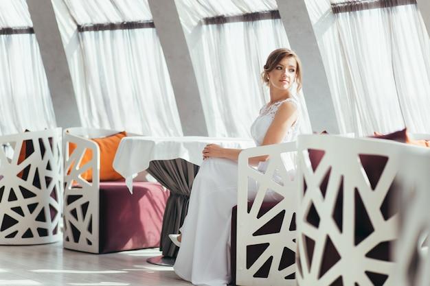Panna młoda siedzi w restauracji. na tle białych dużych okien